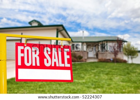Real estate sign in front of a house for sale focus on the sign - stock photo