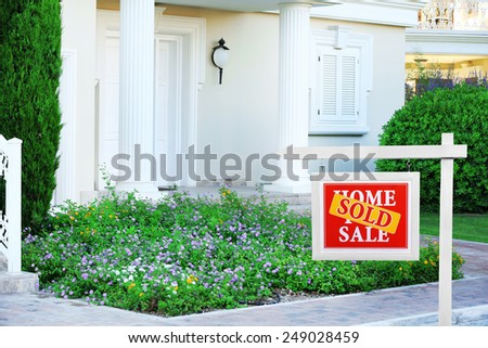 Real estate sign in front of new house. Sold home for sale - stock photo