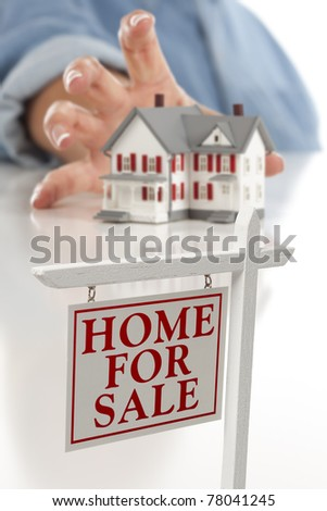 Real Estate Sign in Front of Woman's Hand Reaching for Model House on a White Surface. - stock photo