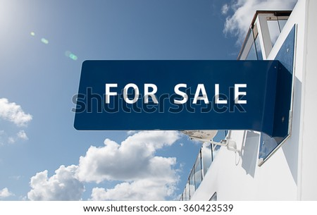 "Real estate sign with text: ""For Sale"" Building with blue sky background."