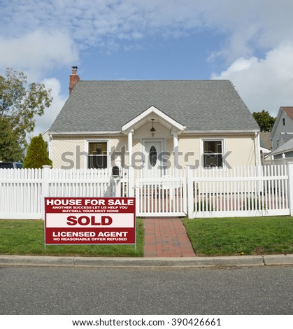 Real estate sold (another success let us help you buy sell your next home) sign Beautiful Bungalow Home with white picket fence sunny blue sky clouds day residential neighborhood USA - stock photo