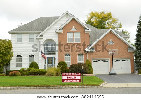 Real estate sold (another success let us help you buy sell your next home) sign Beautiful suburban McMansion Brick Two Car Garage Overcast Day Residential Neighborhood USA - stock photo