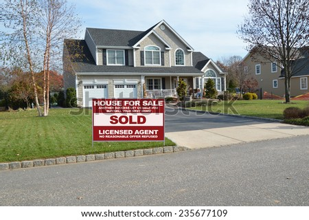 Real Estate sold (another success let us help you buy sell your next home) sign curbside Suburban McMansion home autumn day residential neighborhood USA - stock photo