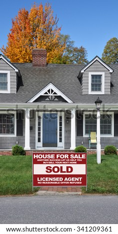 Real estate sold (another success let us help you buy sell your next home) sign Home Entrance Suburban Cape Code Style House Autumn Fall Season Residential Neighborhood USA - stock photo