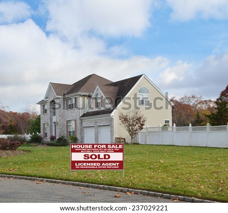 Real Estate sold (another success let us help you buy sell your next home) sign Suburban brick McMansion style home with two car garage white picket fence residential neighborhood blue sky clouds USA - stock photo