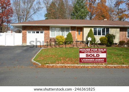 Real estate sold (another success let us help you buy sell your next home) sign suburban brick ranch style home white picket fence blacktop driveway autumn blue sky day residential neighborhood USA - stock photo