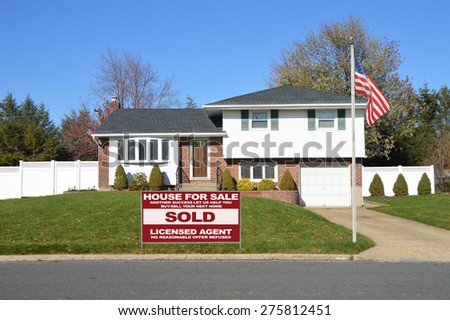 Real estate sold (another success let us help you buy sell your next home) sign Suburban Brick Brownstone Home Autumn blue sky day residential neighborhood USA  - stock photo