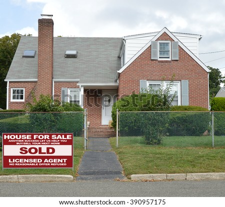 Real estate sold (another success let us help you buy sell your next home) sign Suburban Brick Bungalow Home with Chain Link Fence Blacktop Walkway Blue Sky Clouds Day Residential Neighborhood USA - stock photo
