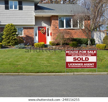 Real estate sold (another success let us help you buy sell your next home) sign suburban brick high ranch home sunny residential neighborhood USA