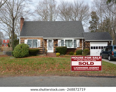 Real estate sold (another success let us help you buy sell your next home) sign Suburban Brown Wood Shingle Cape Cod style home Autumn day residential neighborhood USA - stock photo