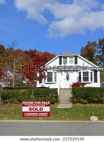 Real Estate sold (another success let us help you buy sell your next home) sign Suburban bungalow style house autumn day in residential neighborhood blue sky clouds USA