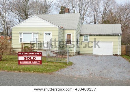Real estate sold (another success let us help you buy sell your next home) sign Suburban Bungalow Home Chain link Fence Overcast day residential neighborhood USA - stock photo