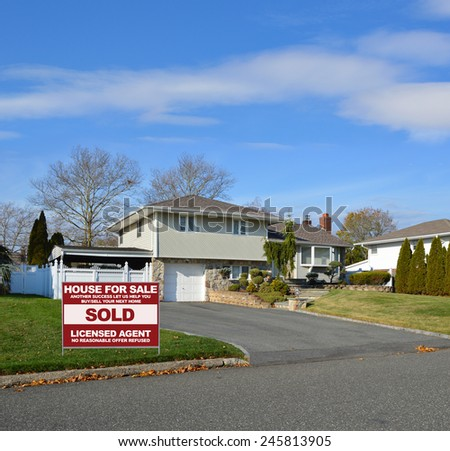 Real estate sold (another success let us help you buy sell your next home) sign Suburban High Ranch Home with Siding and Stone Landscaped beautiful sunny blue sky clouds residential neighborhood USA - stock photo