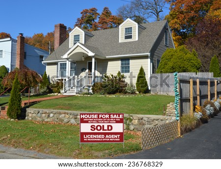 Real Estate sold (another success let us help you buy sell your next home) sign Suburban home autumn day residential neighborhood blue sky USA - stock photo