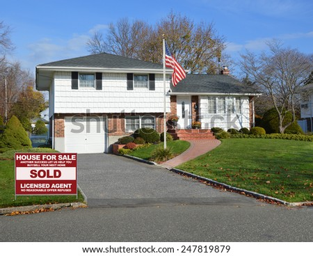 Real estate sold (another success let us help you buy sell your next home) sign Suburban home autumn day residential neighborhood USA