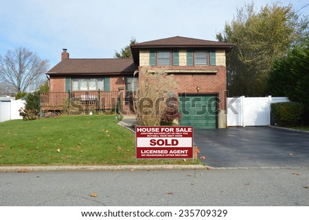 Real Estate sold (another success let us help you buy sell your next home ) sign suburban home back split snout style in residential neighborhood USA