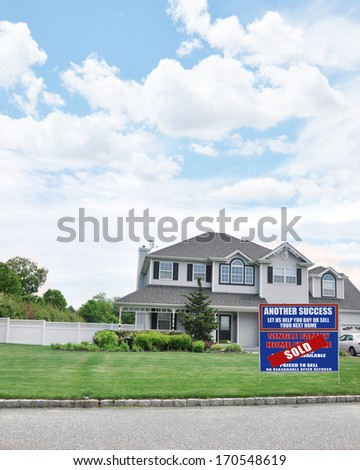 Real Estate Sold (Another Success Let Us Help You Buy Sell Your Next Home) Sign Suburban McMansion Style Home Blue Sky Clouds Residential USA Neighborhood - stock photo