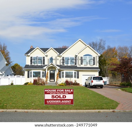 Real estate sold (another success let us help you buy sell your next home) sign Suburban McMansion home autumn day blue sky residential neighborhood USA - stock photo