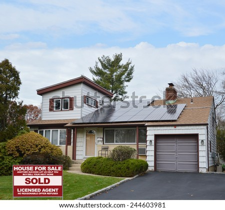 Real Estate sold (another success let us help you buy sell your next home) sign Suburban Ranch style home with solar panel on roof residential neighborhood USA blue sky clouds