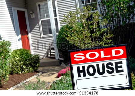 Real estate sold rider insert on a Realtor house for sale sign in the front yard of a resale home under purchase contract  - stock photo
