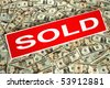 Real estate sold sign over money blanket of assorted dollar bills - stock photo