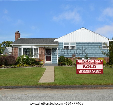 Real Estate sold sign Suburban home ranch style house bay window USA blue sky clouds