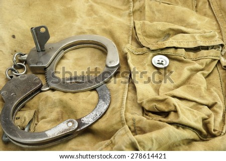 Real Handcuffs With Key, Security Concept On Camouflage Backpack Background - stock photo