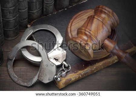Real Handcuffs, Wooden Judge Gavel And Old Law Books On The Rough Brown Wooden Table Background. Arrest in the Courtroom Concept Or Release From Custody - stock photo