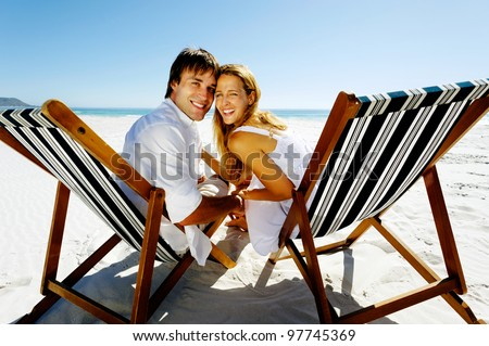 Real happy couple on a summer beach holiday pose for a portrait together, laughing and smiling with pure joy - stock photo