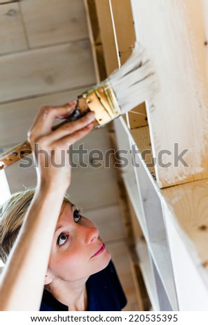 Real Home Renovation (not studio) - Woman Applying White Paint on a Wood Library. - stock photo