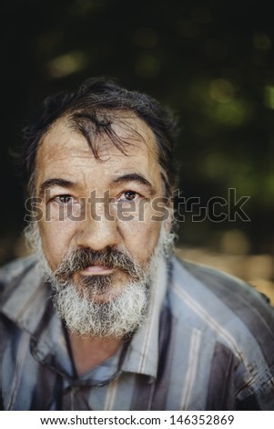 real homeless man on the foliage background, selective focus on eye