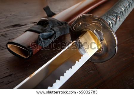Real japanese samurai sword and sheath on wooden board - stock photo