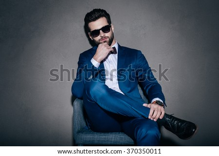 Real macho. Young handsome man in sunglasses and suit keeping hand on chin and looking at camera while sitting on the chair against grey background - stock photo