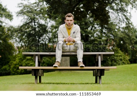 Real man well dressed staying on a bench having a white suit - stock photo