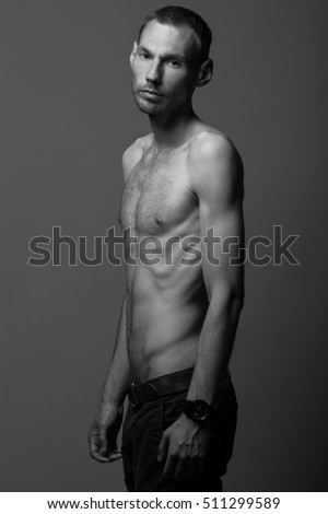 Real natural male beauty concept. Portrait of handsome charismatic man in pants posing over gray background in black and white colors. Classic style. Monochrome studio shot