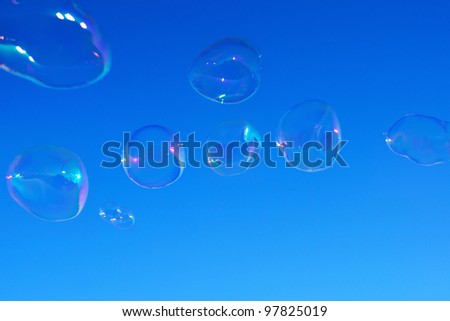 Real natural shaped soap bubbles over clear blue sky. Useful for background - stock photo