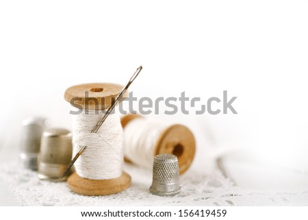 real old reels spools  an old thimble and lace backdrop, shallow dof - stock photo