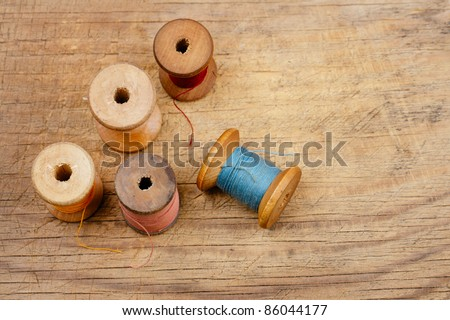 real old reels spools with color treads on old wooded background - stock photo