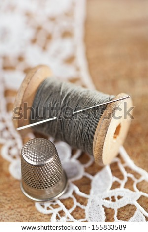 real old reels spools with color treads with thimble and lace backdrop, shallow dof - stock photo