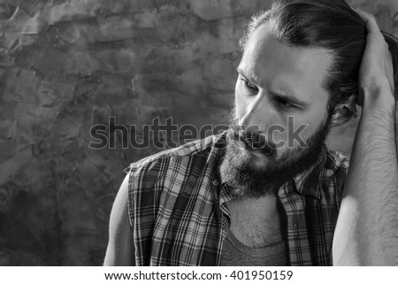 Real old school. Black and white shot of a handsome bearded hipster pulling his hair back against the wall.