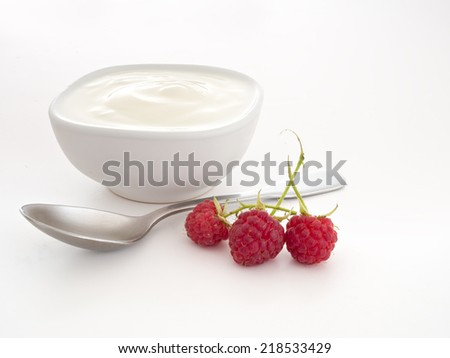 Real organic yoghourt. With spoon, raspberries on white. - stock photo
