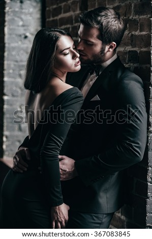 Real passion. Beautiful young loving couple bonding to each other while both standing against brick wall indoors - stock photo