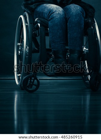 Real people, disability and handicap concept. Young woman invalid girl sitting on wheelchair part of body studio shot on black