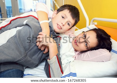 Real people in real situation, sad middle-aged woman lying in hospital with pneumonia, son visit his mother - stock photo