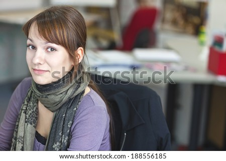Real People - Portrait of a smart and handsome young woman in office with available light - stock photo