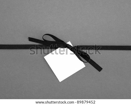 Real Ribbon Bow with Blank Note card Tag on Plain Gray Background - stock photo