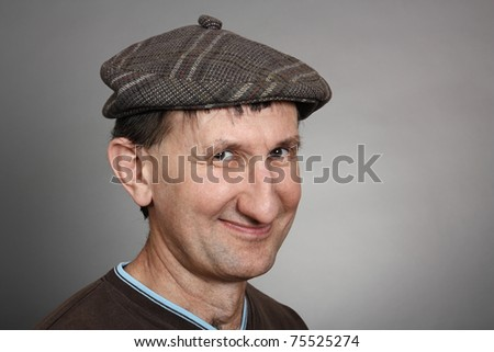 Real smiling man in a cap with a gray background