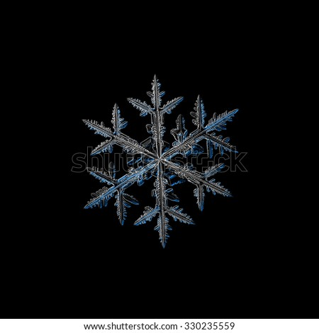 Real snowflake photo (medium size stellar dendrite crystal), isolated on black background