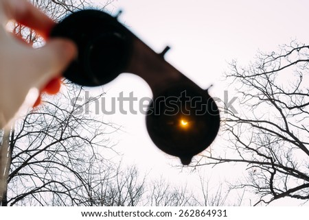 Real Solar Eclipse On March 20, 2015. Moon Covering Sun In Partial Eclipse. Hand Holding A Special Safety Glasses With Tinted Lenses Through Which You Can See The Solar Eclipse - stock photo