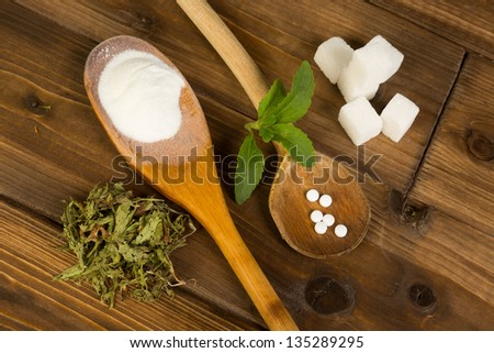 Real sugar lumps and stevia in powder dried and tablet form - stock photo